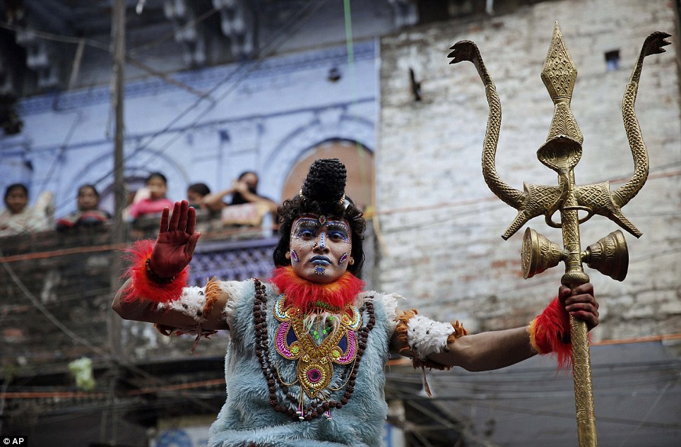 Deity: A man dressed as the Hindu god Lord Shiva offers blessings to the crowd during the Shivaratri procession through the streets of Allahbad