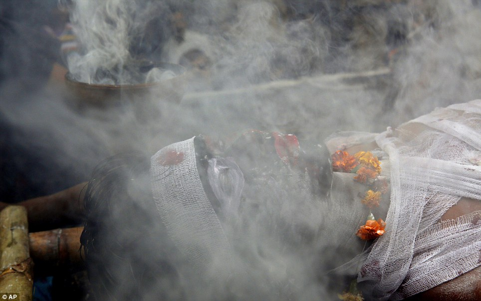 Smoky! A worshipper dressed as a demon lies shrouded in smoke from a fake funeral pyre during the Shivrati celebrations in Allahbad