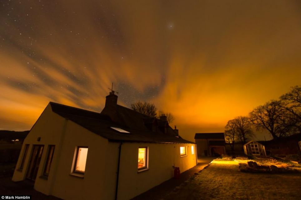Mesmerising: A beautiful display of lights is pictured above the house in Carrbridge - giving the property warm yellow glow