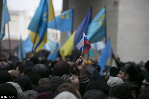 An ethnic Russian Ukrainian holds a Russian flag as Crimean Tatars rally near the Crimean parliament building