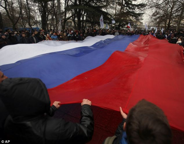 Pro-Russian demonstrators march with a huge Russian flag during a protest in front of a local government building in Simferopol, Crimea