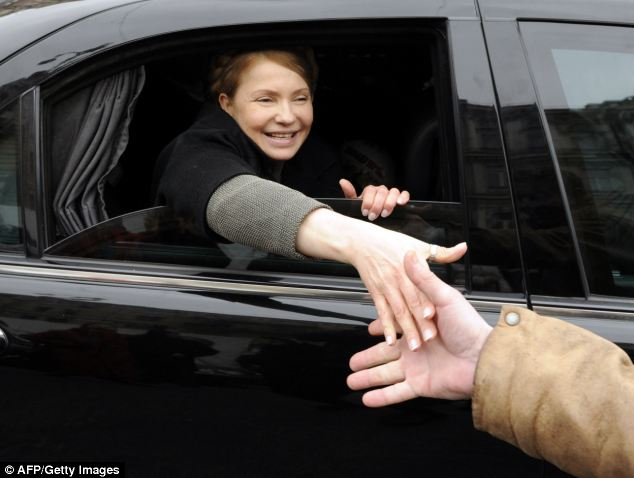 Ukrainian opposition leader Yulia Tymoshenko shakes hands with a man as she arrives to visit the tent camp of her supporters in the center of Kiev today
