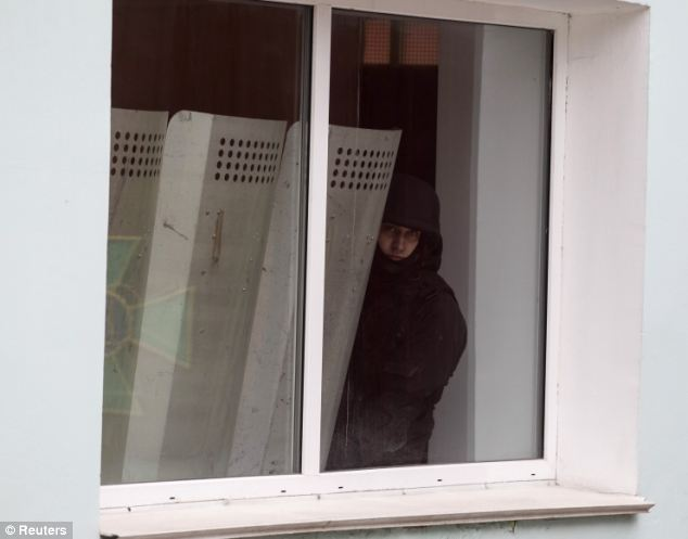 An armed Ukrainian border guard looks out of a window as the base is surrounded by armed Russian navy servicemen in Balaclava