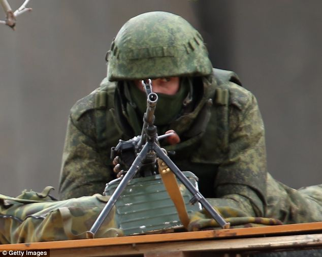 A soldier without identifying insignia mans a machine gun outside the Crimean parliament building