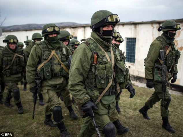 Armed men in military uniform walk outside the territory of a Ukrainian military unit in the village of Perevalnoye, outside Simferopol, where a tense stand-off took place