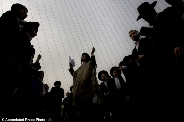 Ultra-Orthodox Jewish men pray during a rally attended by hundreds of thousands against plans to force them to serve in the Israeli military, blocking roads and paralyzing Jerusalem (pictured)