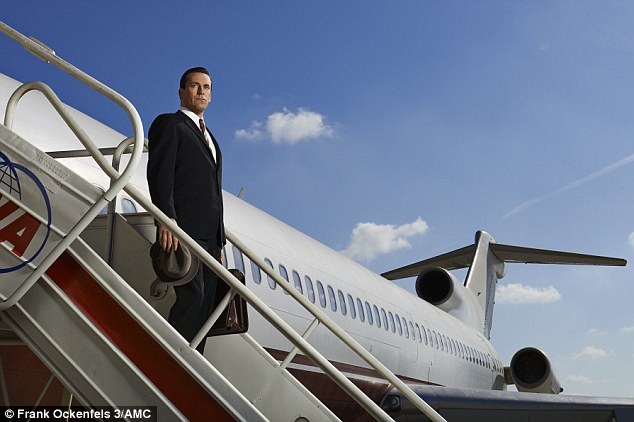 Don Draper holding a fedora in one hand and a briefcase in the other, standing on steps at the side of a TWA plane.