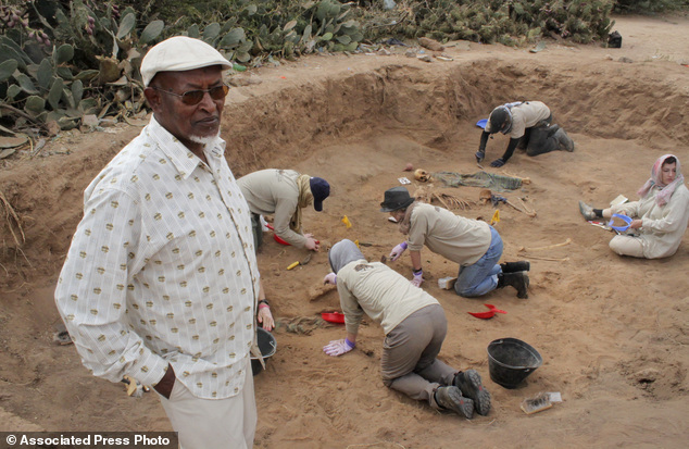 In this photo taken Tuesday, Feb. 18, 2014, Chairman of the Somaliland War Crimes Commission Kadar Ahmed, left, oversees members of the Peruvian Forensic Ant...