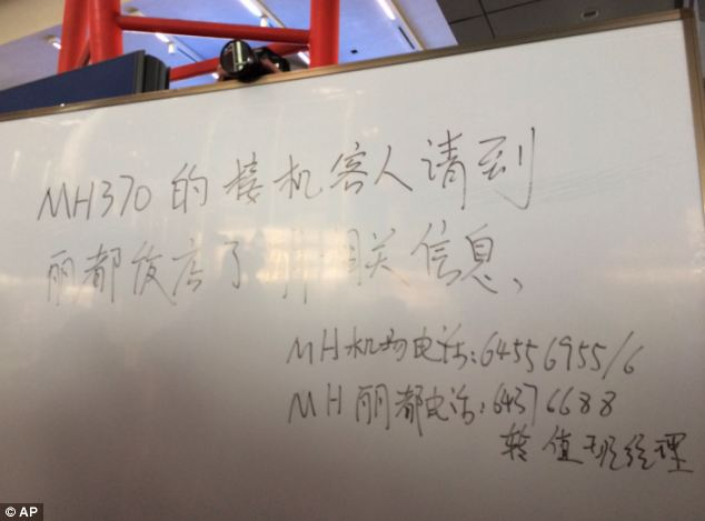 Notice: A message written on a board at Beijing Airport tells relatives the Malaysian Airlines flight MH370 is delayed
