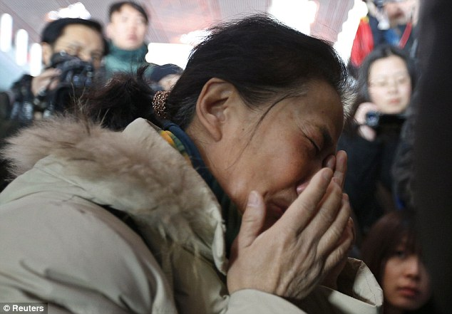 Devastating: A woman cries in Beijing airport as she waits to hear information about her family