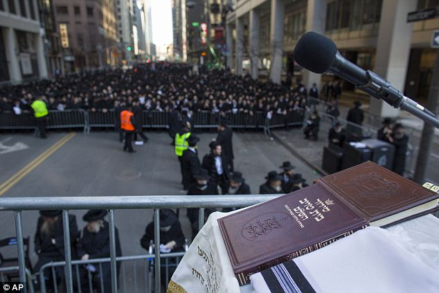 A prayer book lay on a podium as the thousands of Orthodox Jews gather in the background