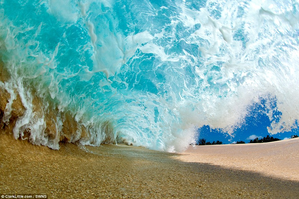 A large wave is captured laying on the dry sand as it throws over to create the shorebreak barrel. Seconds after the shot, Mr Little was washed up onto the beach - his whole body covered in sand