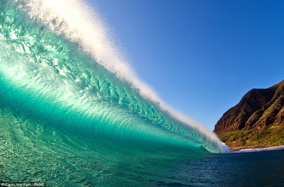 In this picture the wind was blowing strongly offshore, creating a mist flying off the top of this backlit wave on the West Shore, Oahu, Hawaii