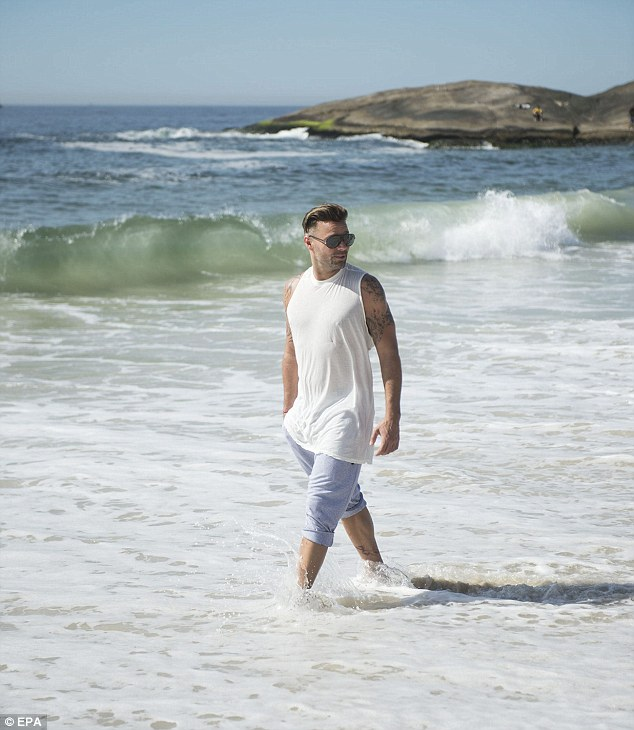 Change in scenery: He then changed into a long white sleeveless shirt and took a walk through the picturesque waters of a Brazilian beach