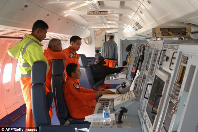 Indonesian Air Force personnel aboard an Indonesian Air Force military surveillance aircraft over the Malacca Strait as they search for the missing Malaysia Airlines flight MH370