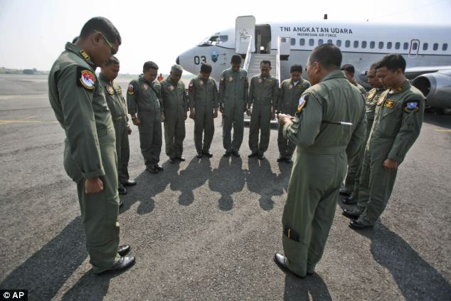 Indonesian Air Force crewmen of a Boeing 737 'Surveiller' maritime patrol aircraft of the 5th Air Squadron 'Black Mermaids' pray prior to a search operation for the missing Malaysia Airlines Boeing 777