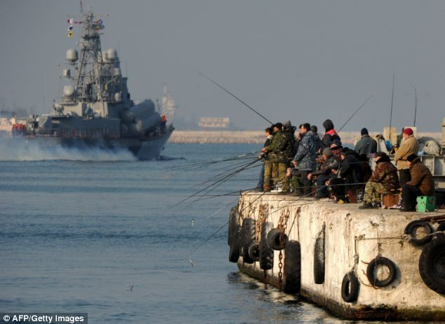 Crimean fishermen on a pier as a Russian naval vessel passes them in Sevastopol Bay