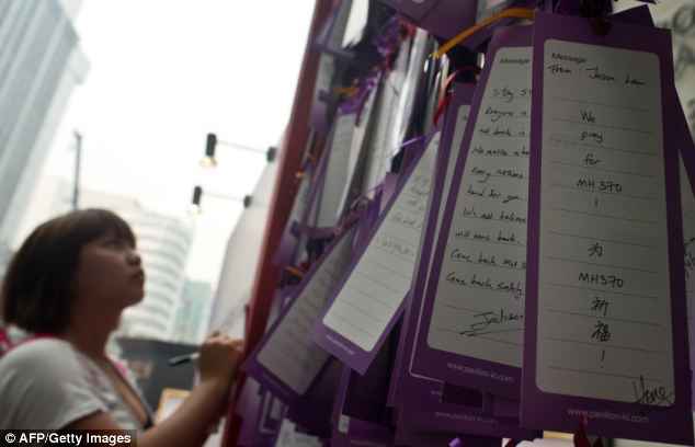 A woman writes a message with others expressing prayers and well-wishes for passengers onboard missing Malaysia Airlines flight MH370, displayed outside a mall in Kuala Lumpur