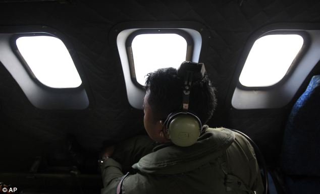 A crew member of a Royal Malaysian Air Force CN-235 aircraft looks out of the window during a search and rescue operation for the missing Malaysia Airlines plane over the Straits of Malacca