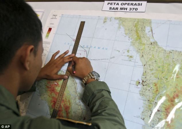 An Indonesian Air Force officer draws a flight pattern flown earlier in a search operation for the missing Malaysia Airlines Boeing 777, during a post-mission briefing at Suwondo air base in Medan, North Sumatra, Indonesia