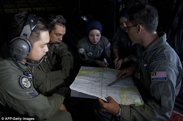 Expanded search: A Royal Malaysian Air Force Navigator captain Izam Fareq Hassan (right) talks with his team members onboard a Malaysian Air Force CN235 aircraft during a search and rescue (SAR) operation