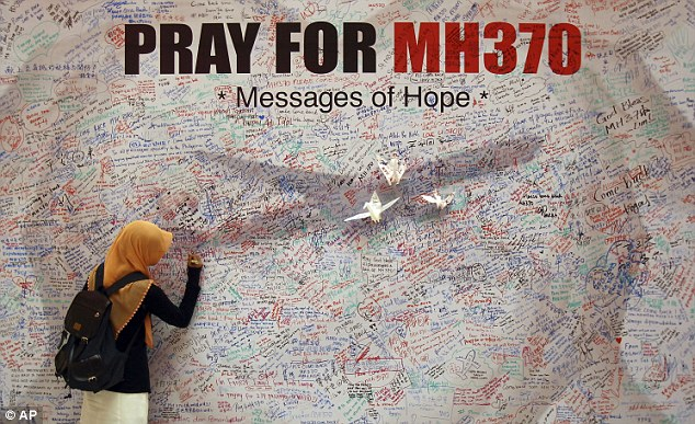 Support: Thousands of people have written messages of support on a wall at a shopping mall in Kuala Lumpur, for passengers on board the missing Malaysia Airlines plane