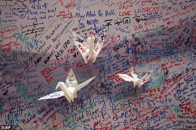 Hope: Paper cranes are pasted on a message board for passengers aboard a missing Malaysia Airlines plane, at a shopping mall in Kuala Lumpur