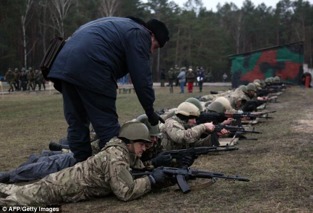 A Ukrainian interim forces officer (left) supervises recruits during a shooting exercise