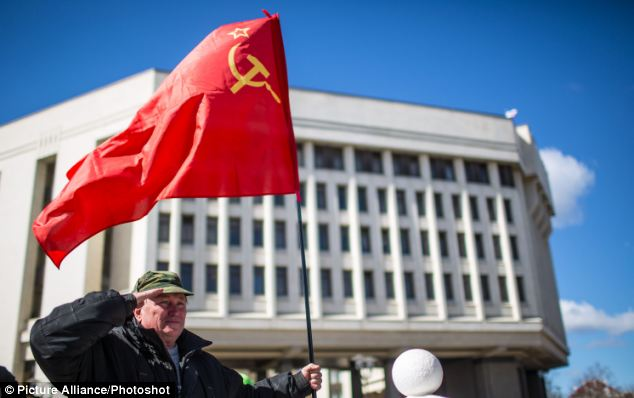 A man holding a Soviet era red flag salutes in front of the parliament building after the end of the referendum in Simferopol, Crimea