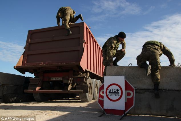 Ukrainian border guards search a truck at a check point on the administrative border of Crimea and Ukraine