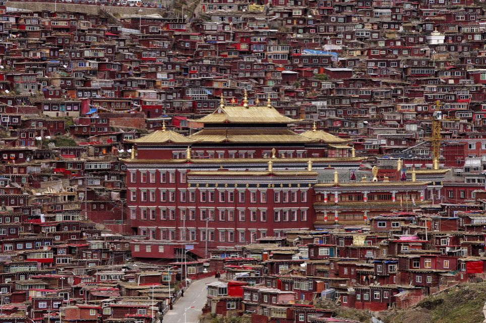 Stunning: Among these rows of simple red houses lies an intellectual hotspot - the world's largest school for Tibetan Buddhism - pictured in the centre