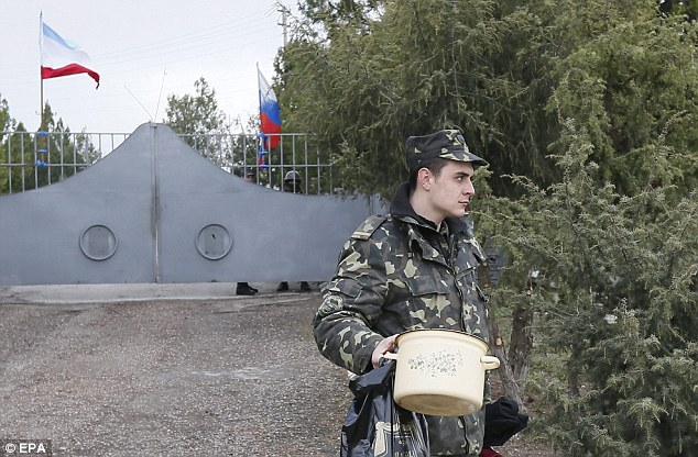 Another base taken over: A Ukrainian serviceman leaves a military unit in Bakhchisarai, outside Simferopol, on Thursday after it was seized by Russian troops on Wednesday night