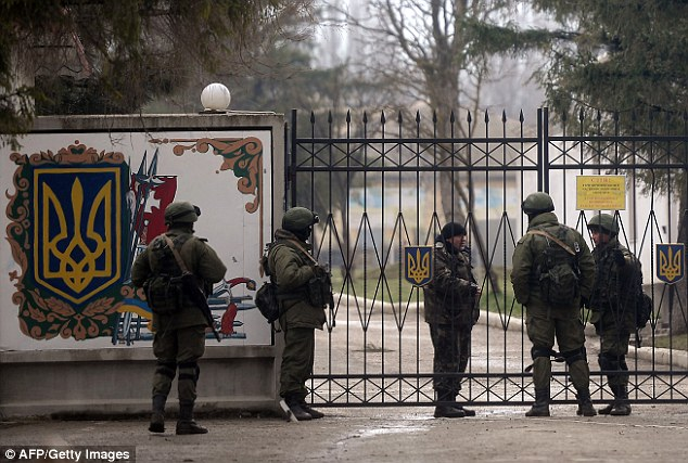 Civil: Russian and Ukranian soldiers talk at the gate of a Ukrainian military unit in the village of Perevalnoye, outside Simferopol, on Thursday