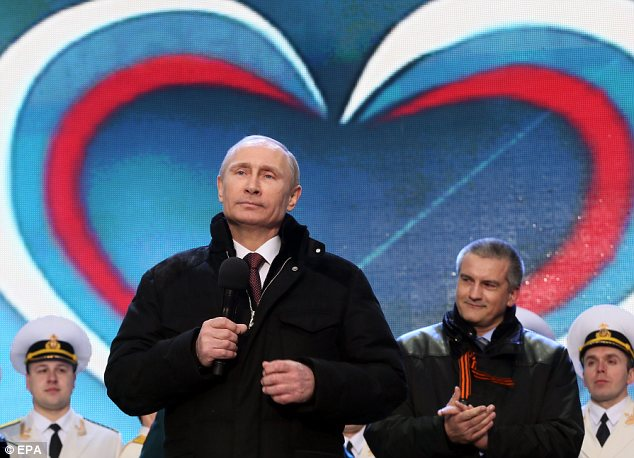 Showman: Russian President Vladimir Putin (L) spoke Tuesday at a rally celebrating his annexation of Crimea and Sevastopol after what the U.S> and other governments called an 'illegal referendum'