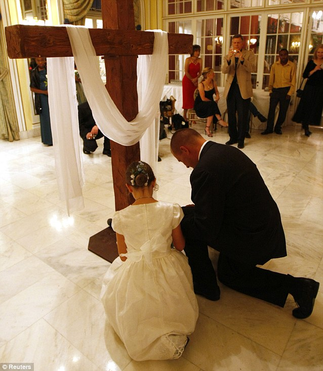 An unidentified father and daughter kneel at a cross after the girls lay white roses symbolising their commitment to purity at a ball