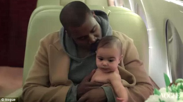 Daddy's girl: Kanye plants a kiss on his bouncing baby's head while sitting on a plane in the video