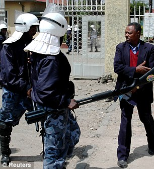 Intimidation: Riot police confront a man (not the claimant) near the Tegbareed Industrial College as officers beat rock-throwing students during a demonstration