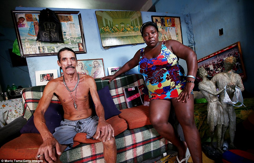 An 'pacification' initiative was launched in 2010 by government forces to reclaim power of the city's slums from armed gangs. Pictured here Louis Carlos de Sousa and Tania Gozalves at their home on the Complexo da Mare