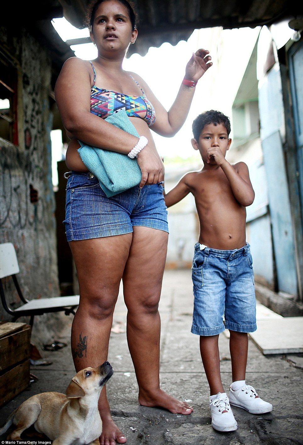 Mother Quiva stands with her son Joao Vitor in the impoverished favela. The Mare complex has more than 13,000 residents