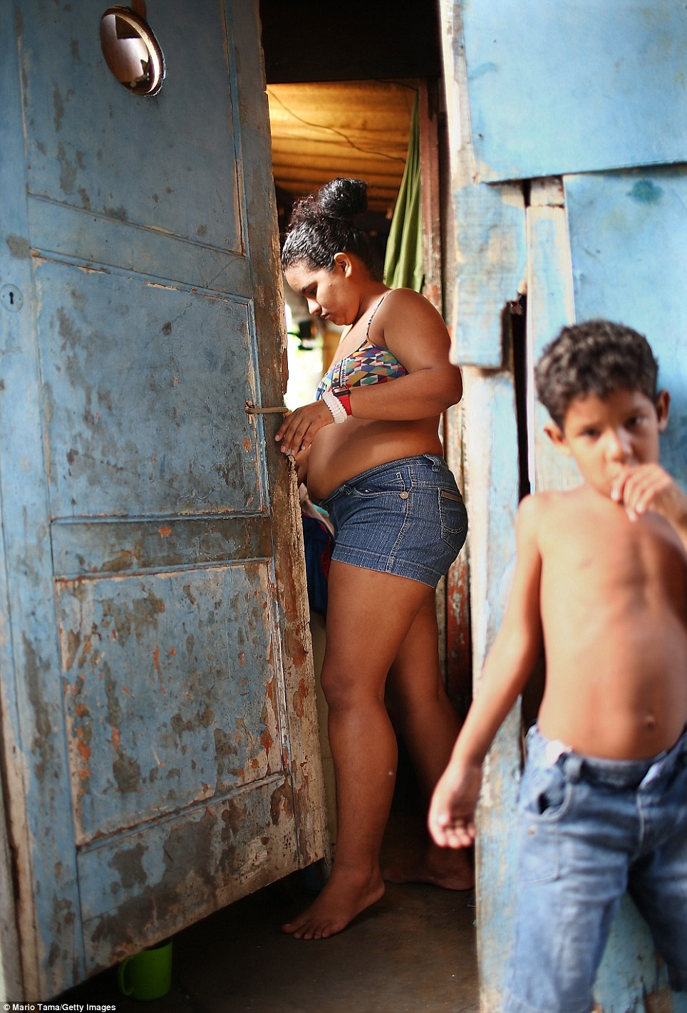 Mother Quiva stands in her home near son Joao Vitor. The police have been the subject of much controversy in the country. Last week. a police headquarters was burned down in a protest against government presence in the favelas