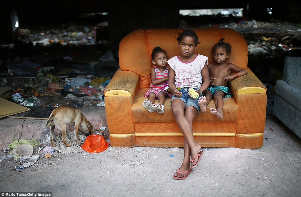 Three children sit on a sofa staring at the camera in the Complexo da Mare slum - one of the largest 'favelas' in Rio de Janeiro. Today, Brazilan government forces will clear out the favela ahead of the World Cup which begins on June 14