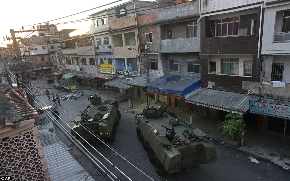 Navy tanks roll through the favela.  The police community pacification unit, known as the UPP, will step in once federal forces have left the area. The UPP will then remain in the shanty town in order to keep peace and control any uprising