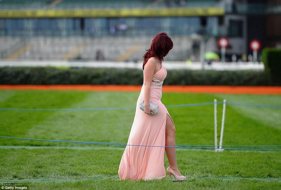 Pretty: A racegoer cuts a striking figure as she wafts across the racecourse in a full-length peach dress ahead of the first race on Ladies Day at Aintree