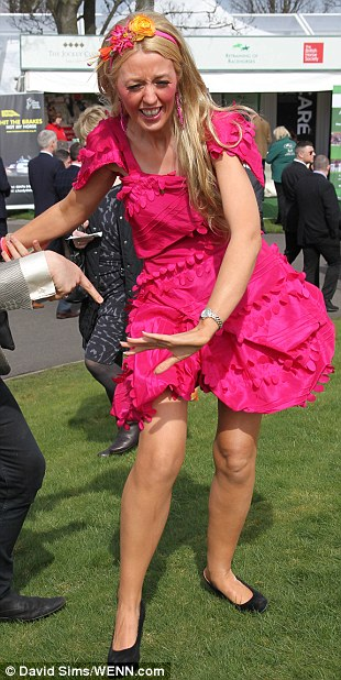 Wobbly: High heels and wet grass don't mix as this girl discovered on a day out at Aintree