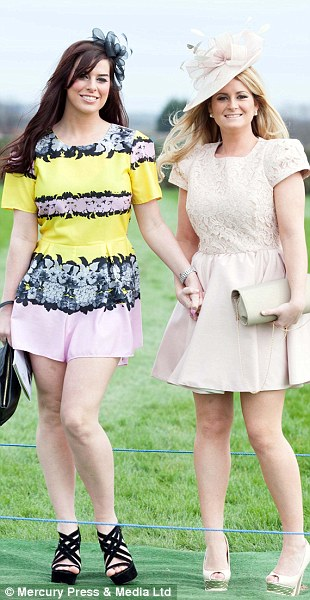 Looking good: Two friends show off their pretty ensembles as they arrive at Aintree