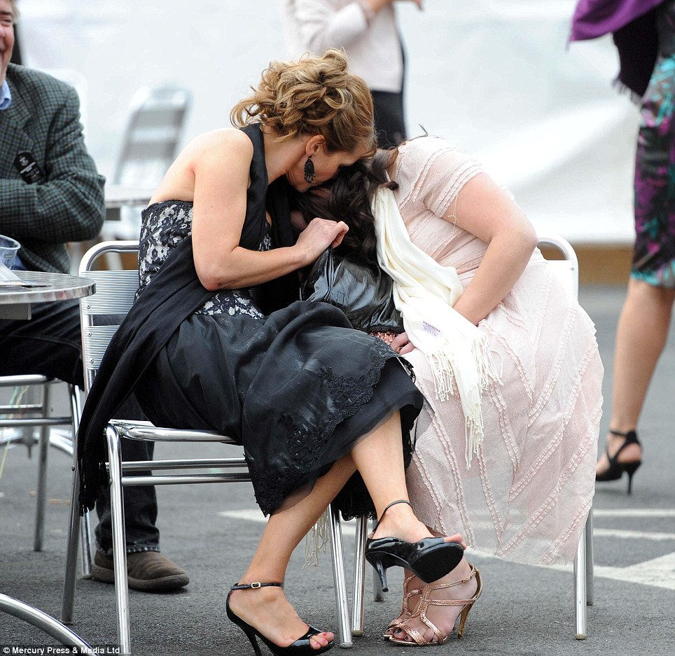 One woman comforts another after a day of drinking at Aintree