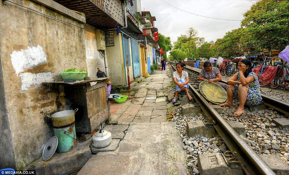 Unusual sight: The photographer said there are barbershops, people selling goods, chefs cooking food and kids running around - 'all within inches of the tracks'