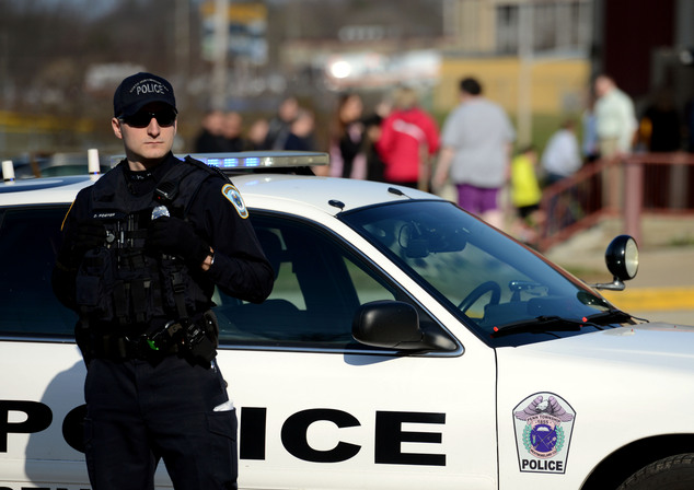 A police officer guards the entrance Heritage Elementary School as students are dismissed after more than a dozen students were stabbed by a knife wielding s...