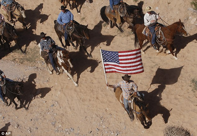 No horsing around: The Bundy family and their supporters fly the American flag as their cattle were released from a corral