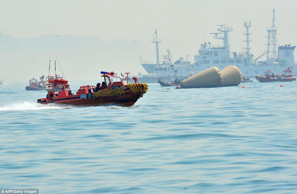 Recovery: South Korean rescue teams take part in recovery operations at the site of the sunken Sewol ferry, marked with buoys, off the coast of the South Korean island of Jindo on Wednesday